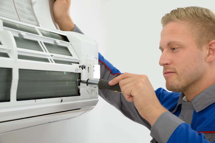 Portrait Of Young Male Technician Repairing Air Conditioner in Mount Vernon, TX.