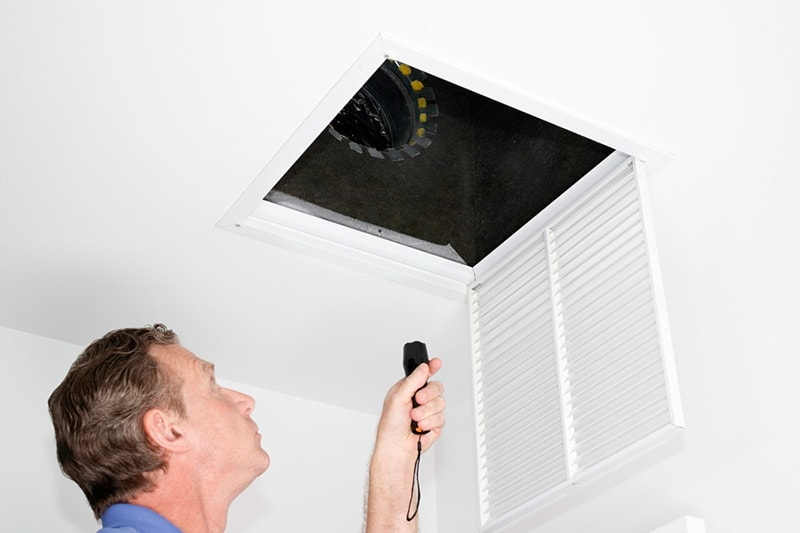 man inspecting ceiling vent